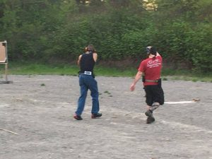 an action shooter moving through a course followed by the RSO / timer