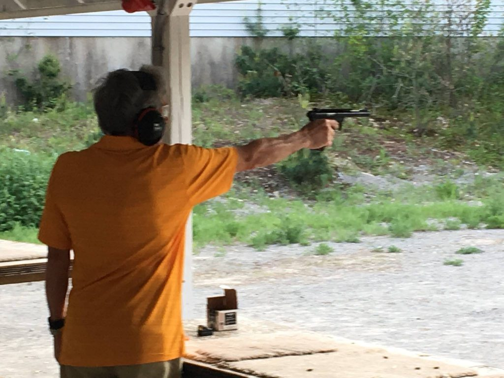 Man shooting a pistol with one hand