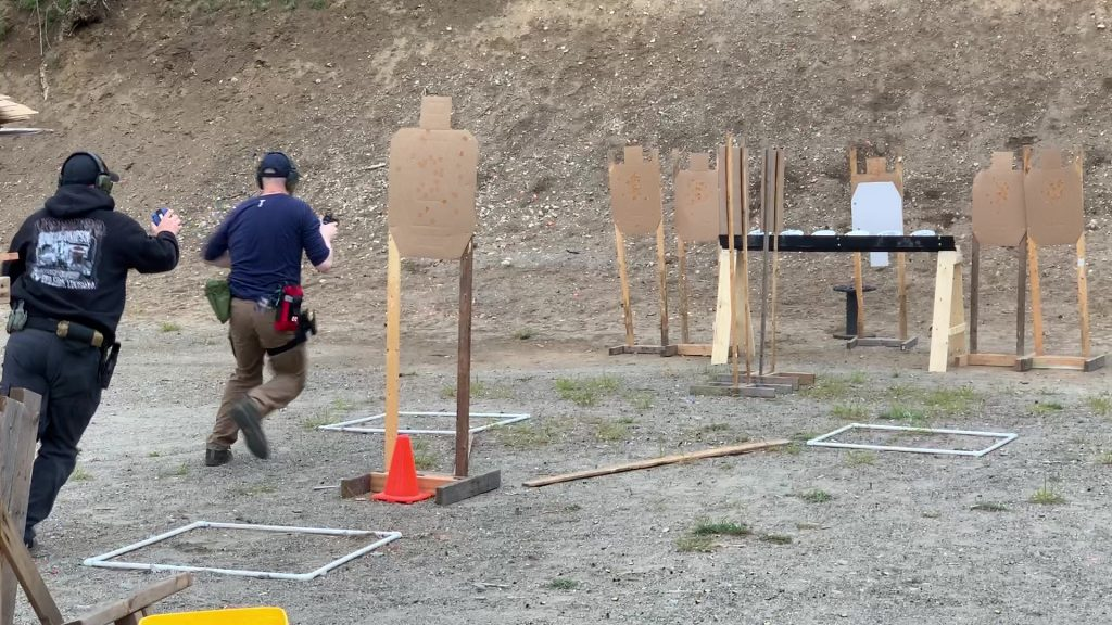 Man moving through a dynamic course with a pistol, followed by the timer/RSO
