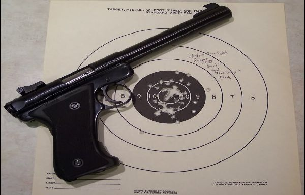 a target pistol laid on a target that has been used