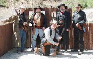 Five armed cowboys in period garb in front of the stockade entrance
